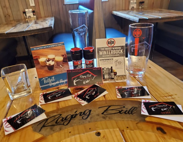 Raging Bull Steakhouse glasses, stickers, and promo cards.